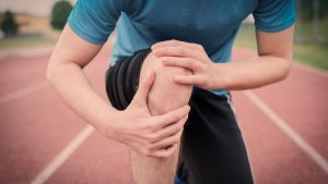 Runner holding knee with pain